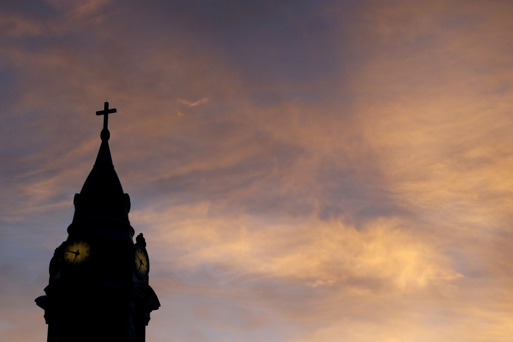 FILE - In this Sept. 27, 2015 file photo, clouds are lit by the rising sun over St. Augustine Roman Catholic Church in Philadelphia.  Pennsylvania's R...