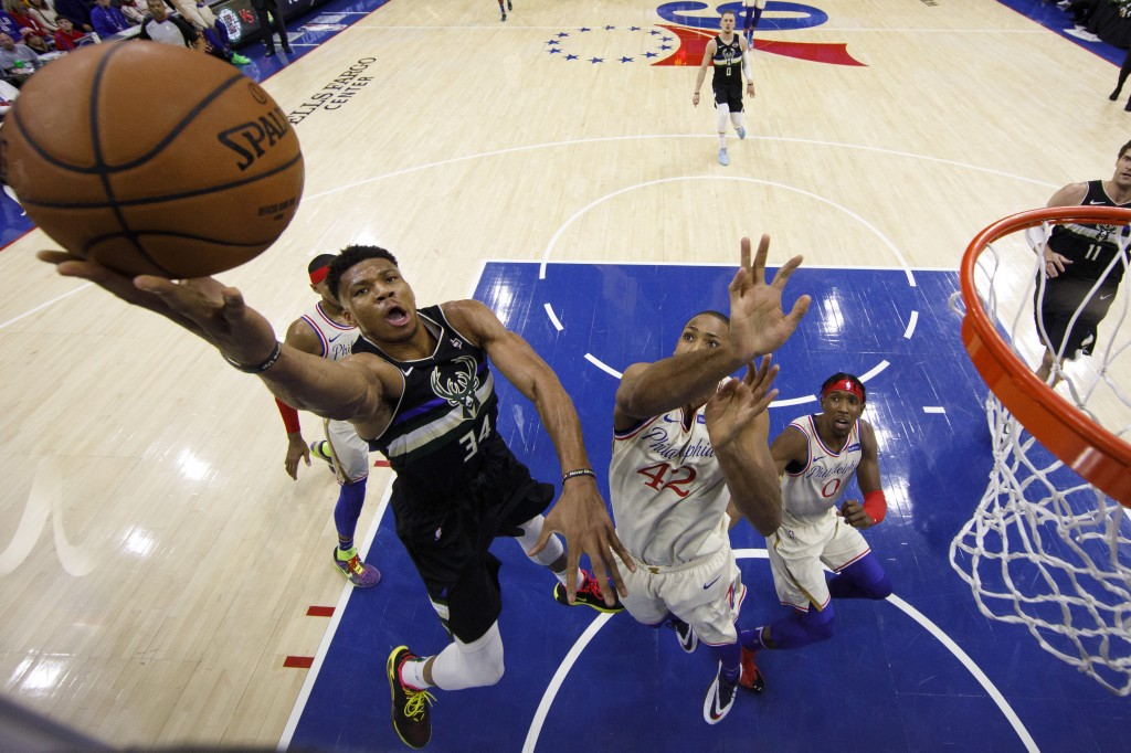 Milwaukee Bucks' Giannis Antetokounmpo, left, goes up for the shot with Philadelphia 76ers' Al Horford, right, defending during the first half of an N...