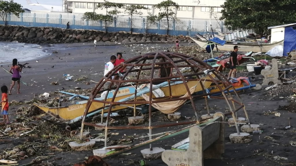 Residents walks beside an outrigger and playground equipment that were damaged by Typhoon Phanfone along a coastline in Ormoc city, central Philippine...