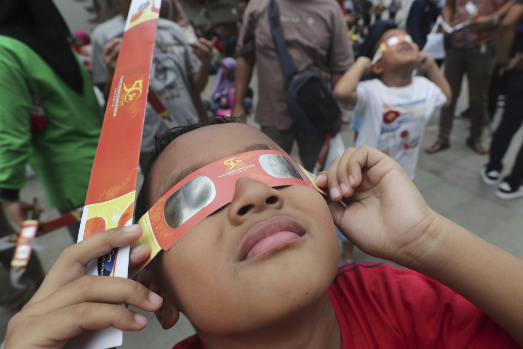 In this Thursday, Dec. 26, 2019, file photo, a child looks up at the sun wearing protective glasses to watch a solar eclipse from Jakarta, Indonesia. ...