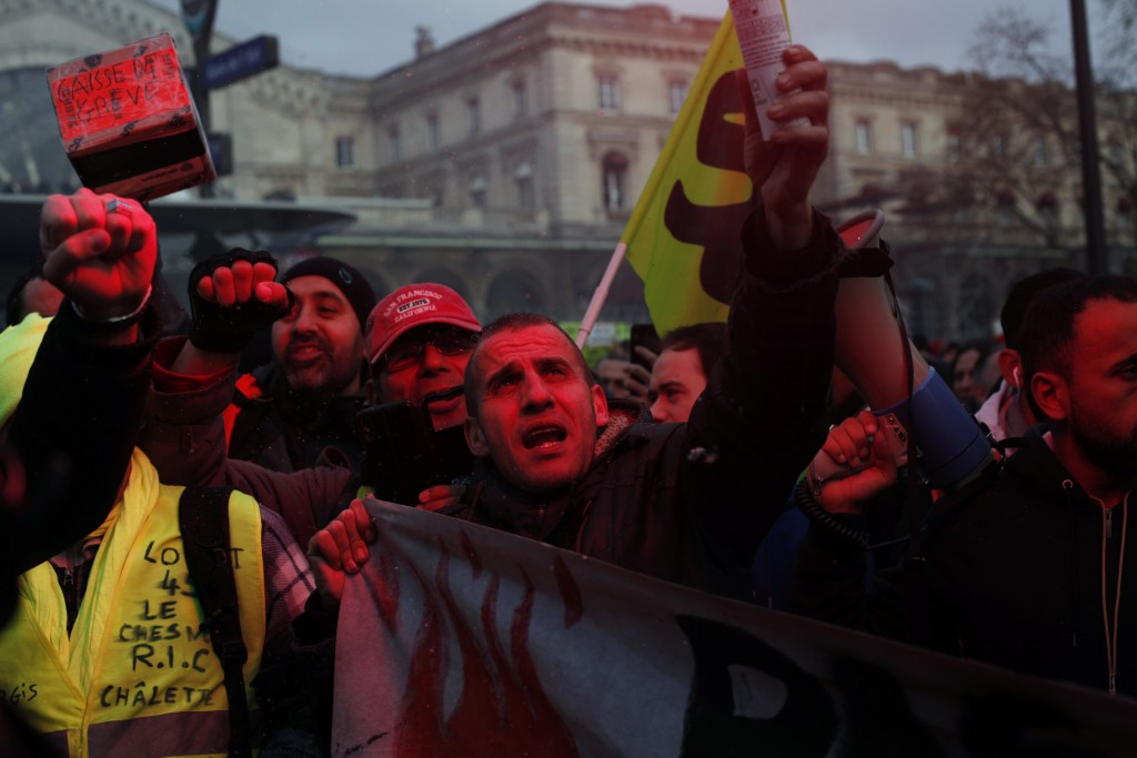 French union members and workers demonstrate after 22 days on a strike against pension reform plans, in Paris, Thursday, Dec. 26, 2019. France's punis...