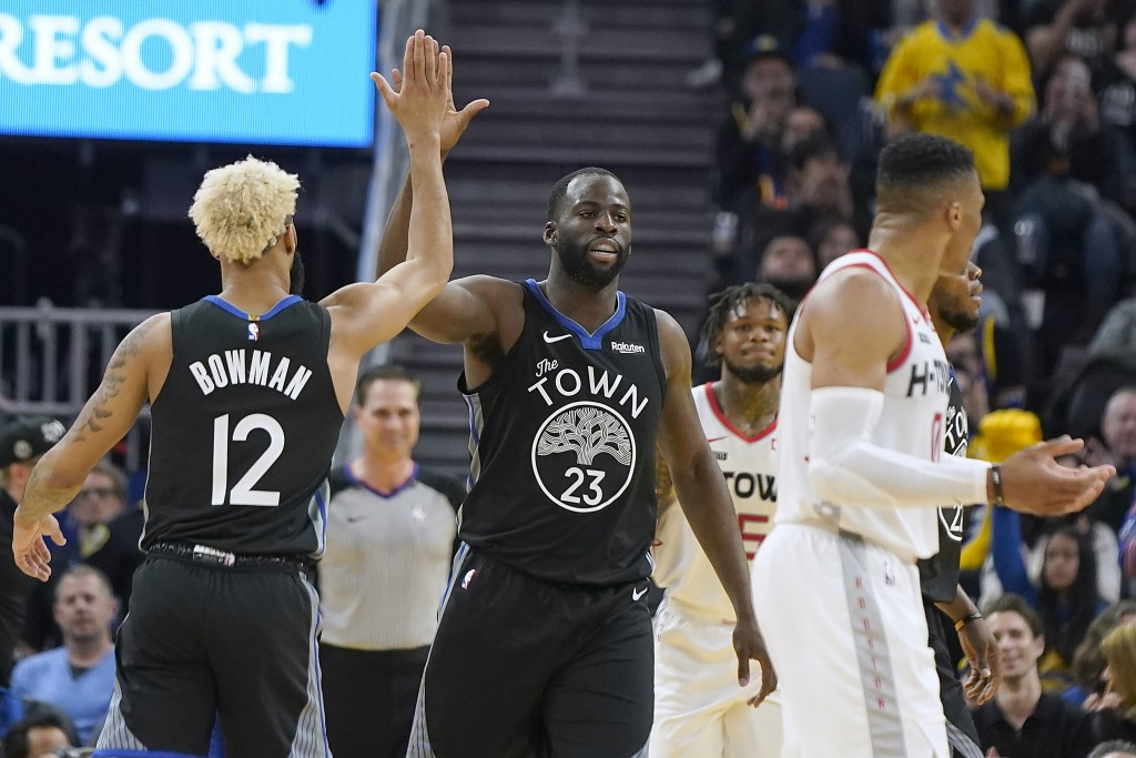 Golden State Warriors forward Draymond Green (23) is congratulated by Ky Bowman (12) after scoring against the Houston Rockets during the first half o...