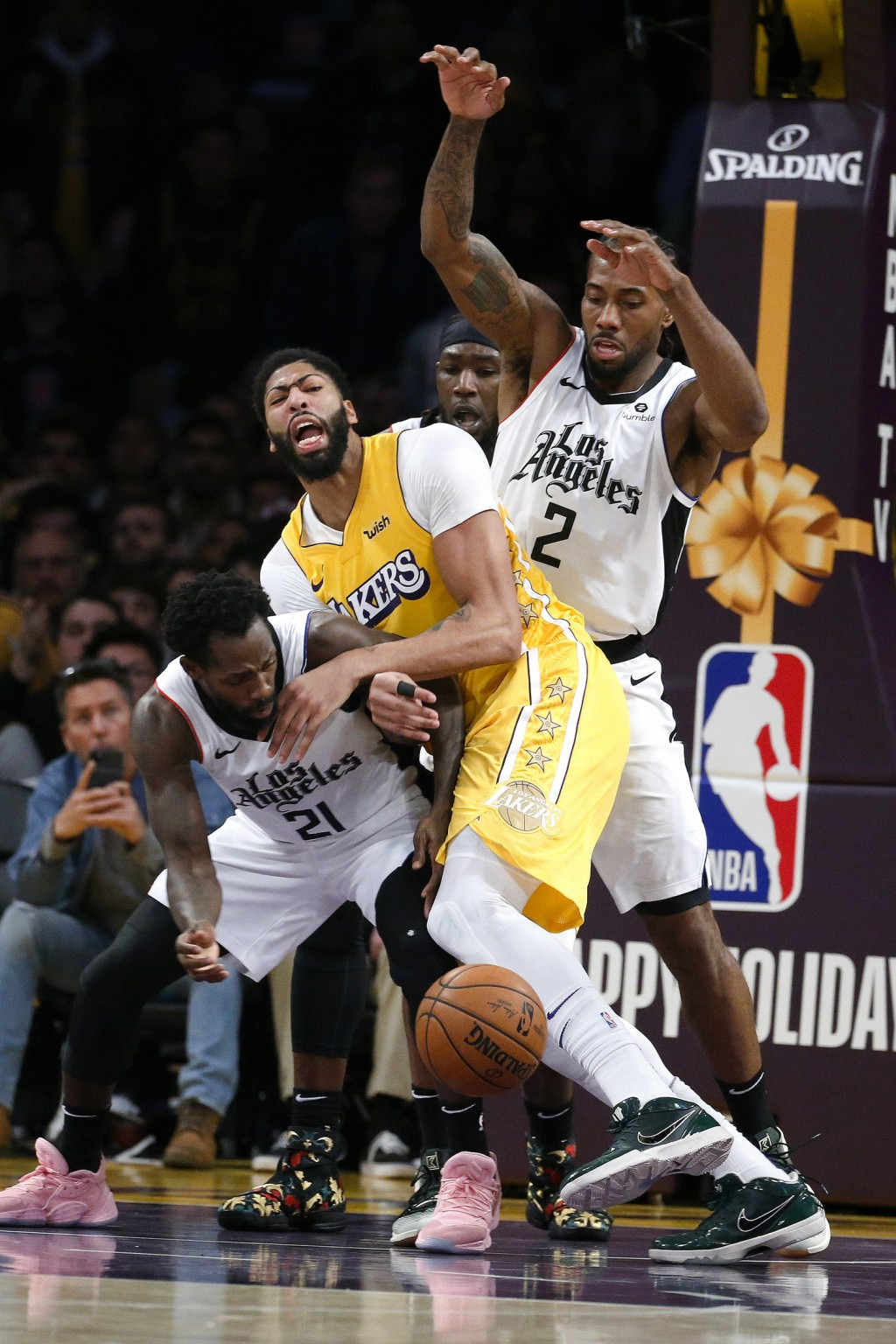 Los Angeles Lakers' Quinn Cook (2) fights for the ball against Los Angeles Clippers' Patrick Beverley (21) and Kawhi Leonard (2) during the second hal...