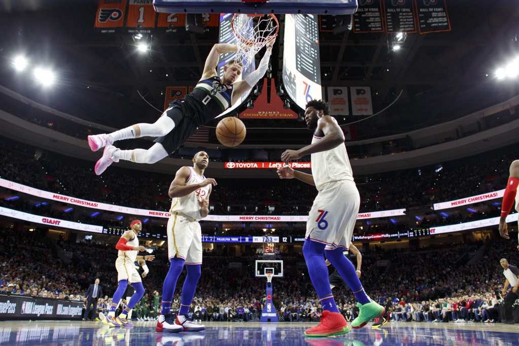 Milwaukee Bucks' Donte DiVincenzo, left, dunks the ball as Philadelphia 76ers' Joel Embiid, right, defended during the first half of an NBA basketball...