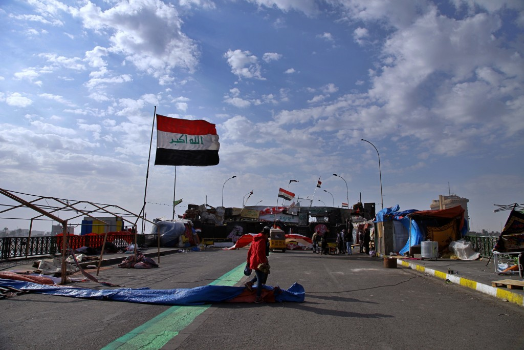 Protesters stage a sit-in on barriers at the Sinak bridge leading to the heavily fortified Green Zone, the seat of Iraq's government, during anti-gove...