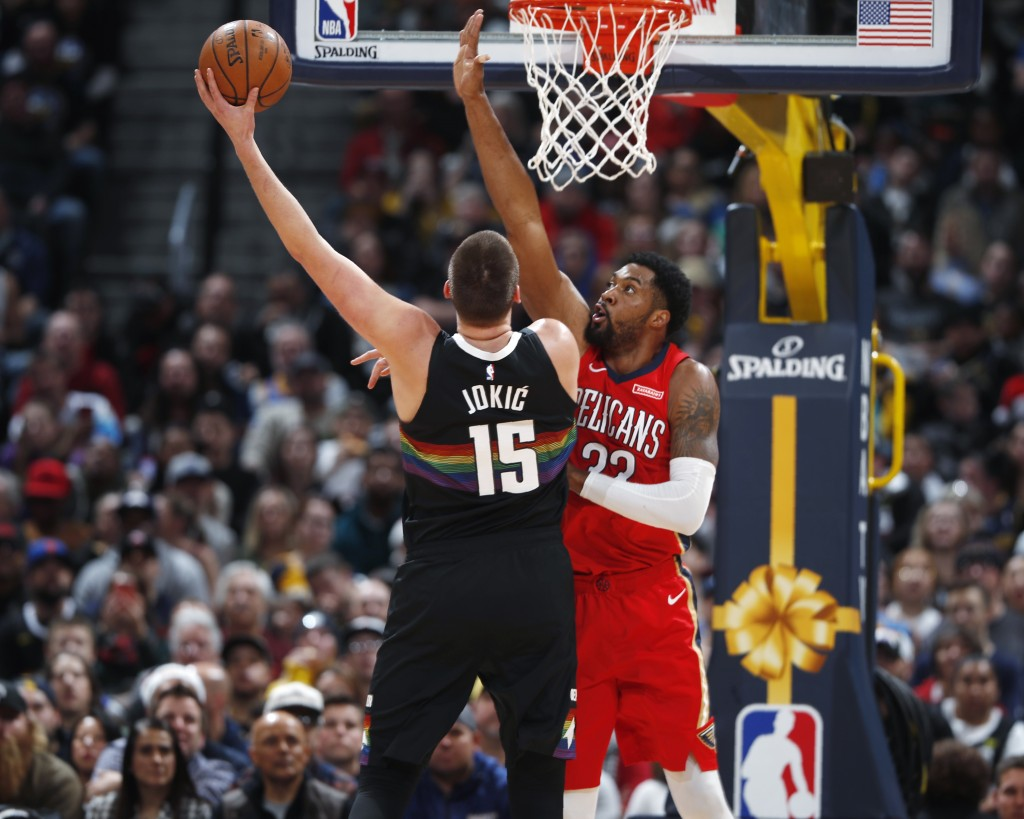 New Orleans Pelicans forward Derrick Favors, right, reaches up to defend against a shot by Denver Nuggets center Nikola Jokic during the first half of...