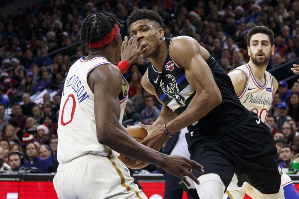 Milwaukee Bucks' Giannis Antetokounmpo, right, drives to the basket as Philadelphia 76ers' Josh Richardson, left, will accidentally pokes him in the e...