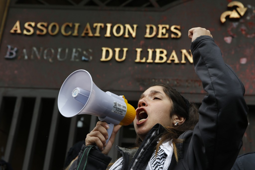 A protester leads a chant during ongoing protests against the Lebanese political class, in front of the building of the Lebanese Association of Banks ...