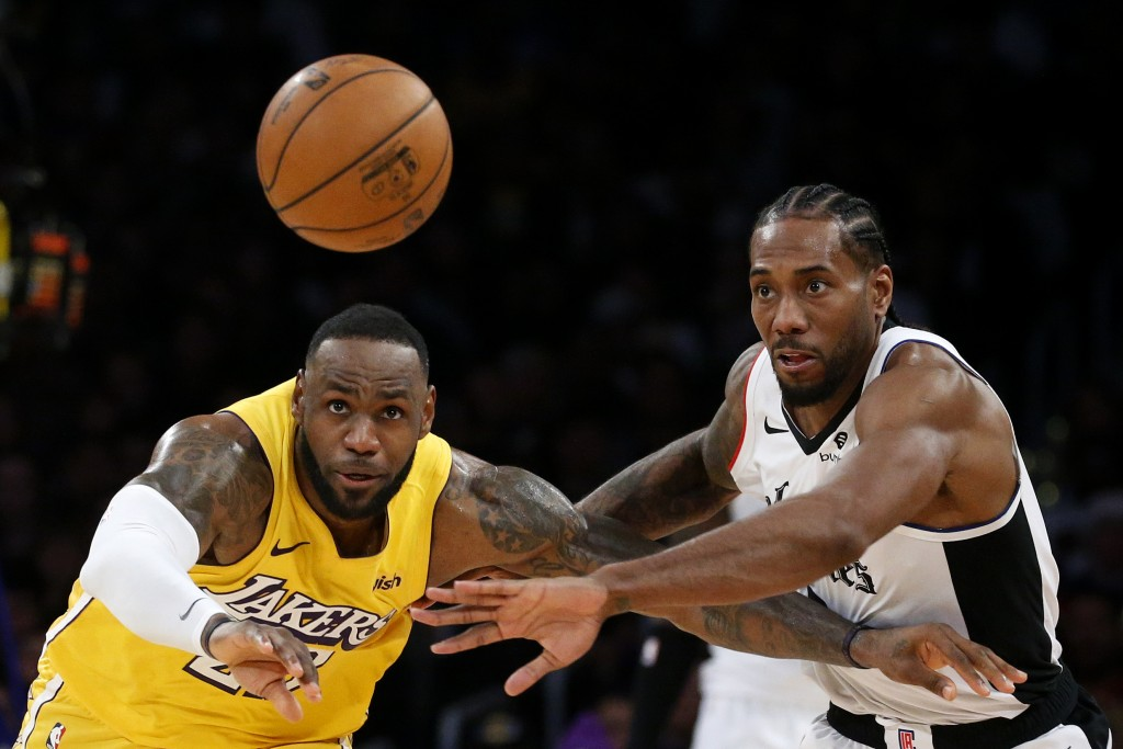 Los Angeles Lakers' LeBron James, left, and Los Angeles Clippers' Kawhi Leonard (2) chase the ball during the second half of an NBA basketball game We...