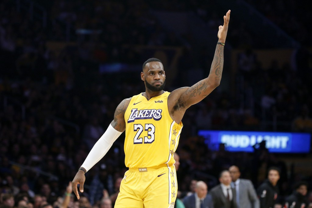 Los Angeles Lakers' LeBron James reacts after making a 3-pointer during the second half of the team's NBA basketball game against the Los Angeles Clip...