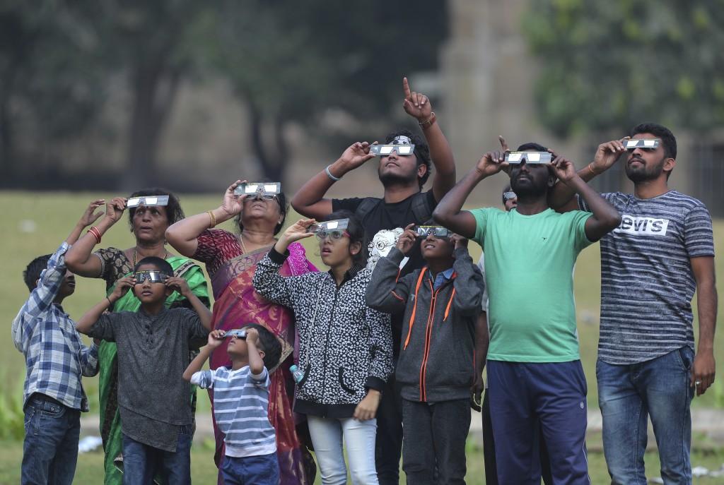 Indians watch a partial solar eclipse in Hyderabad, India, Thursday, Dec. 26, 2019. (AP Photo/Mahesh Kumar A.)