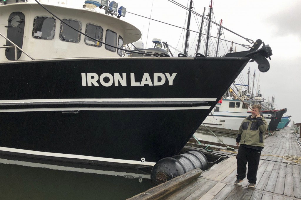 In this Dec. 11, 2019 photo, Kevin Dunn, a trawler who fishes for groundfish, stands next to his boat as he speaks on the phone with a fish processor ...