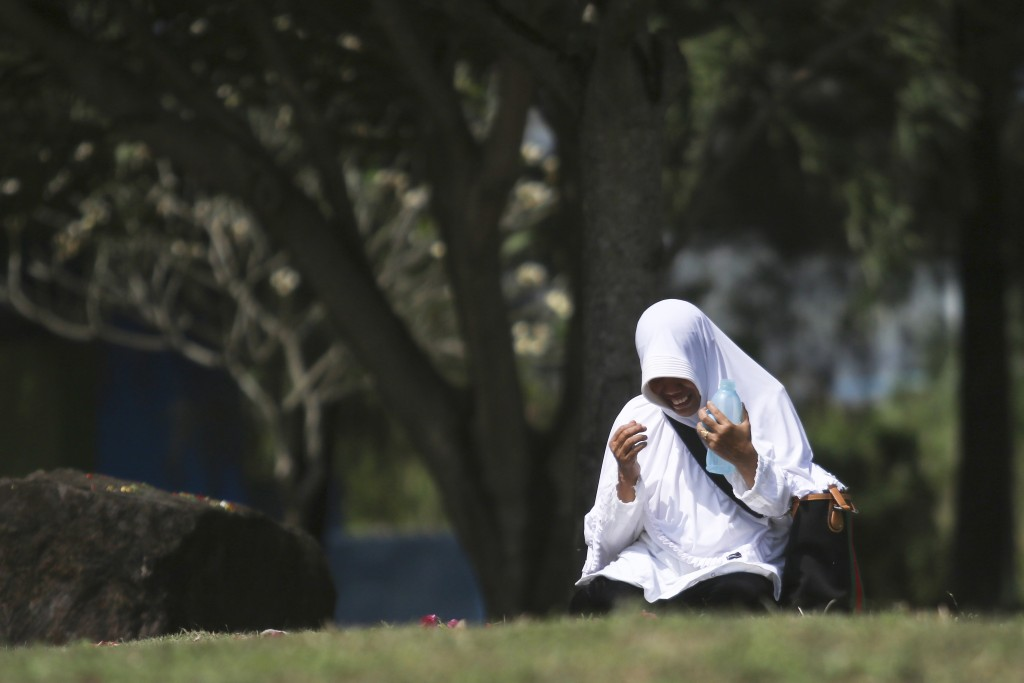 A woman prays at a mass grave for the victims of Indian Ocean tsunami, during the commemoration of the 15th anniversary of the disaster in Banda Aceh,...