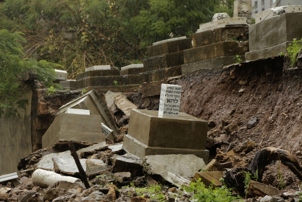 Graves from a Jewish cemetery lie on a sidewalk after it collapsed following heavy rains in the Sodeco area of Beirut, Lebanon, Thursday, Dec. 26, 201...