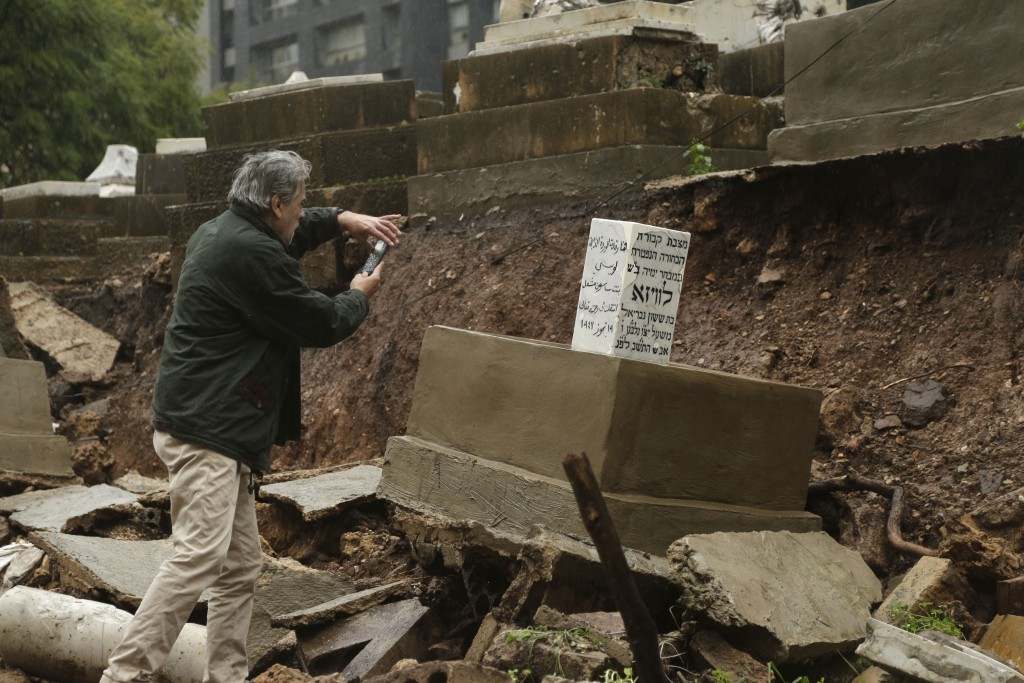 A man takes a picture of graves in a Jewish cemetery damaged from heavy rains in the Sodeco area of Beirut, Lebanon, Thursday, Dec. 26, 2019. A heavy ...