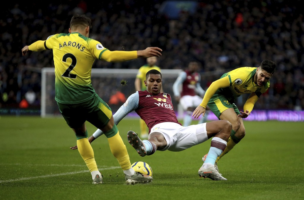 Aston Villa's Wesley, center, battles for the ball with Norwich City's Max Aarons, left, and Emi Buendia during their English Premier League soccer ma...