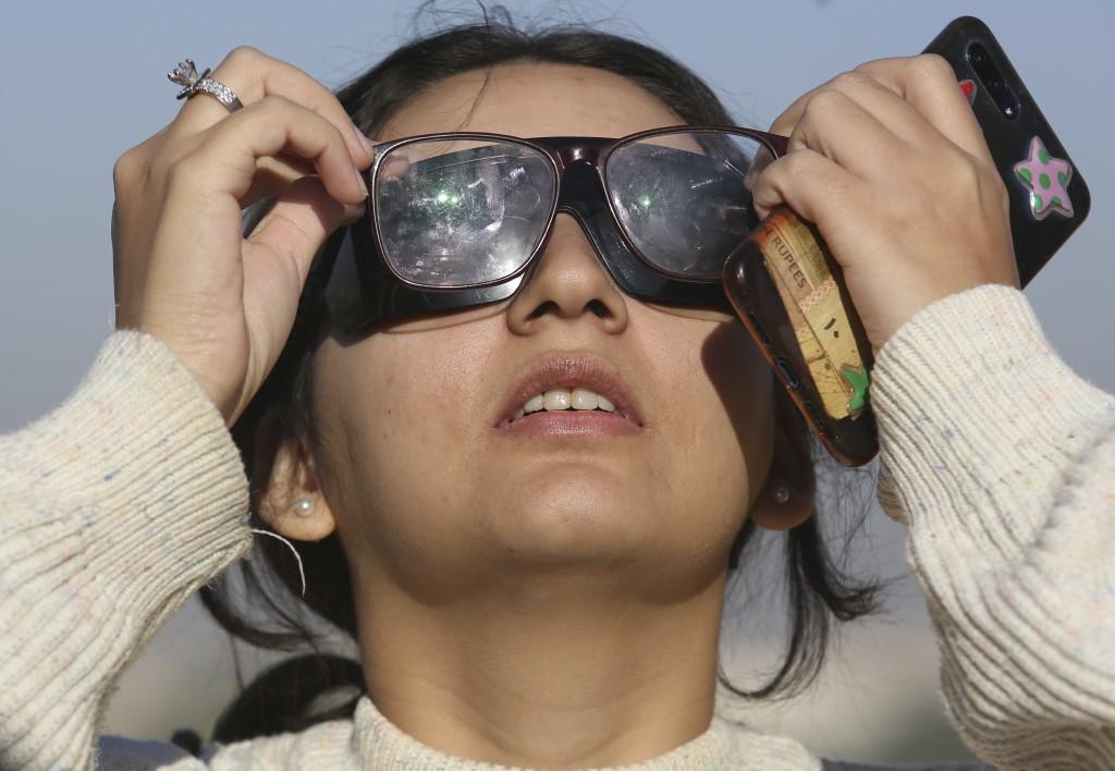 A student of Karachi University views the solar eclipse seen from Karachi, Pakistan, Thursday, Dec. 26, 2019. The last solar eclipse of 2019 was witne...