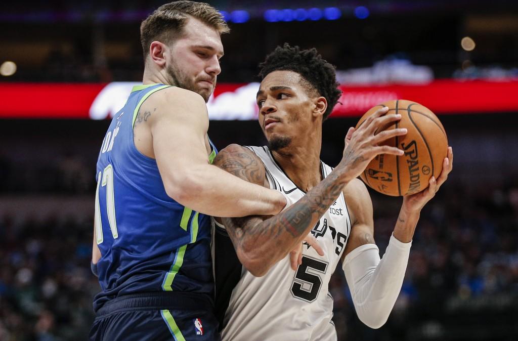San Antonio Spurs guard Dejounte Murray (5) battles Dallas Mavericks forward Luka Doncic (77) for space during the second half of an NBA basketball ga...