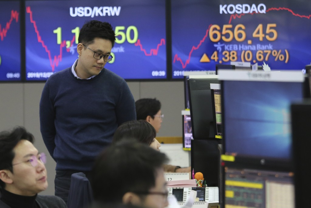 A currency trader watches monitors at the foreign exchange dealing room of the KEB Hana Bank headquarters in Seoul, South Korea, Friday, Dec. 27, 2019...