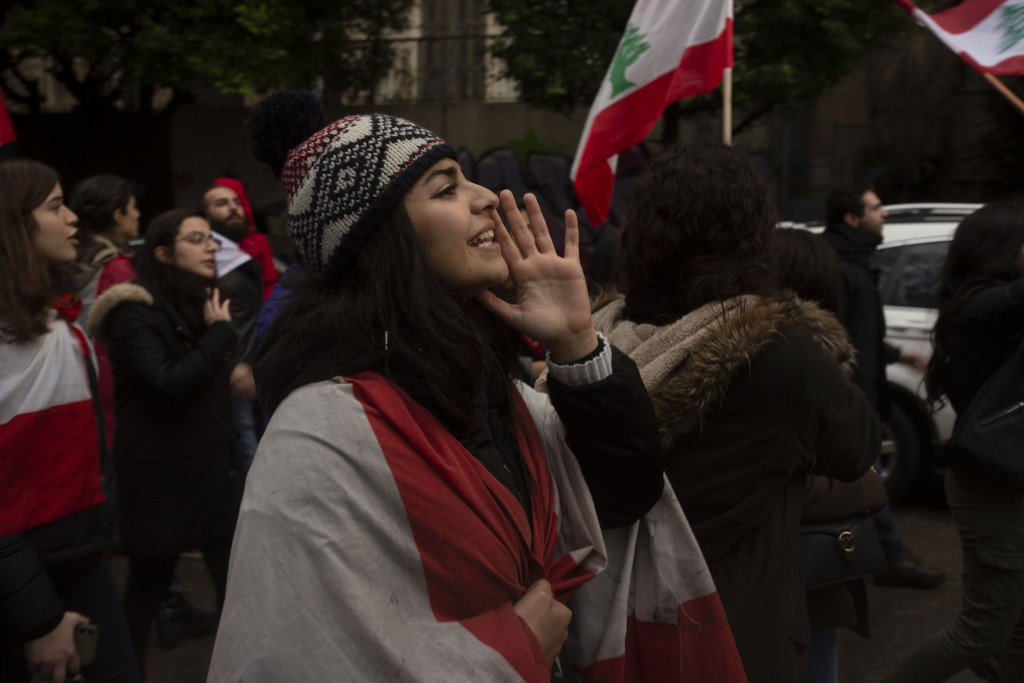 A Lebanese expatriate woman wears the national flag as she chants anti-government slogans at a protest march from the foreign ministry to the Parliame...