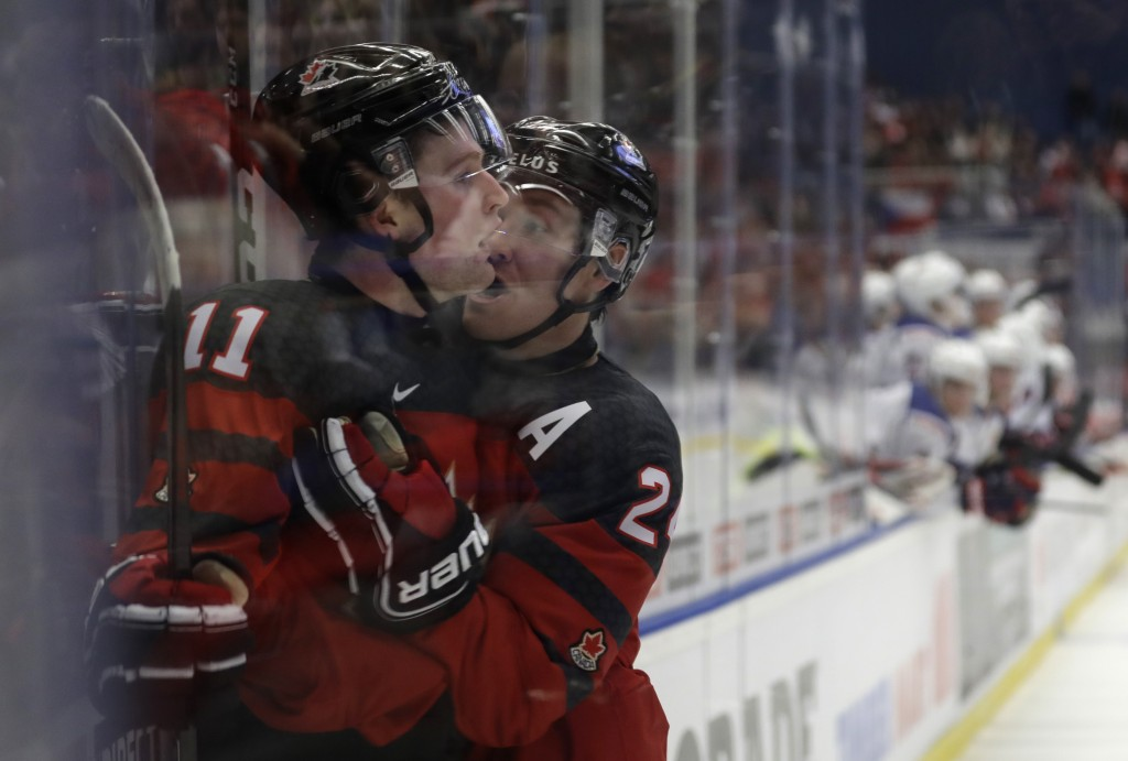 Canada's Alexis Lafreniere, left, celebrates with Canada's Ty Smith, right, after scoring his sides fifth goal during the U20 Ice Hockey Worlds match ...