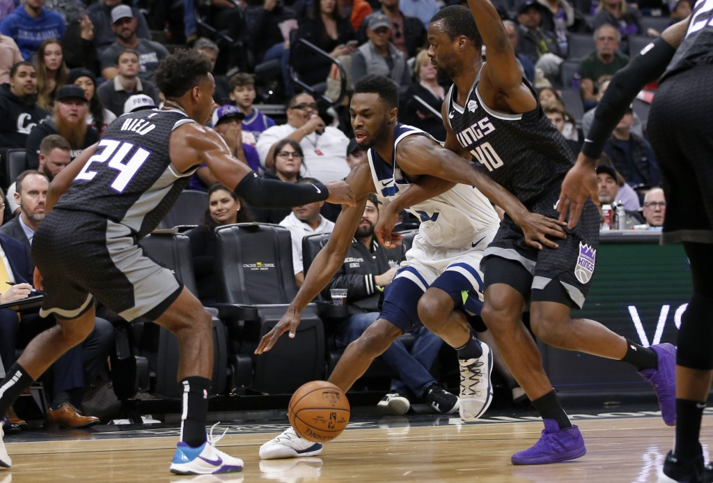 Minnesota Timberwolves forward Andrew Wiggins, center, tries to drive between Sacramento Kings' Buddy Hield, left, and Harrison Barnes, right, during ...