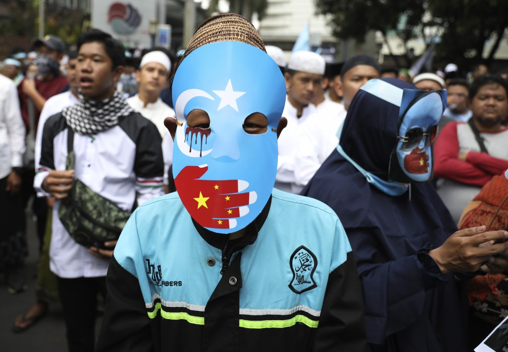 A Muslim youth wears a pro-independence mask with an Eastern Turkistan flag during a rally outside the Chinese Embassy in Jakarta, Indonesia, Friday, ...