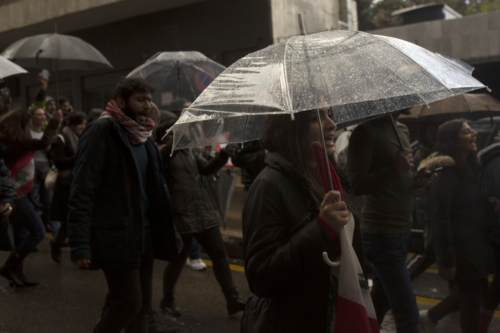 Lebanese expatriates chant anti-government slogans during a protest march headed to the Parliament building under heavy rain Thursday, Dec. 26, 2019 i...