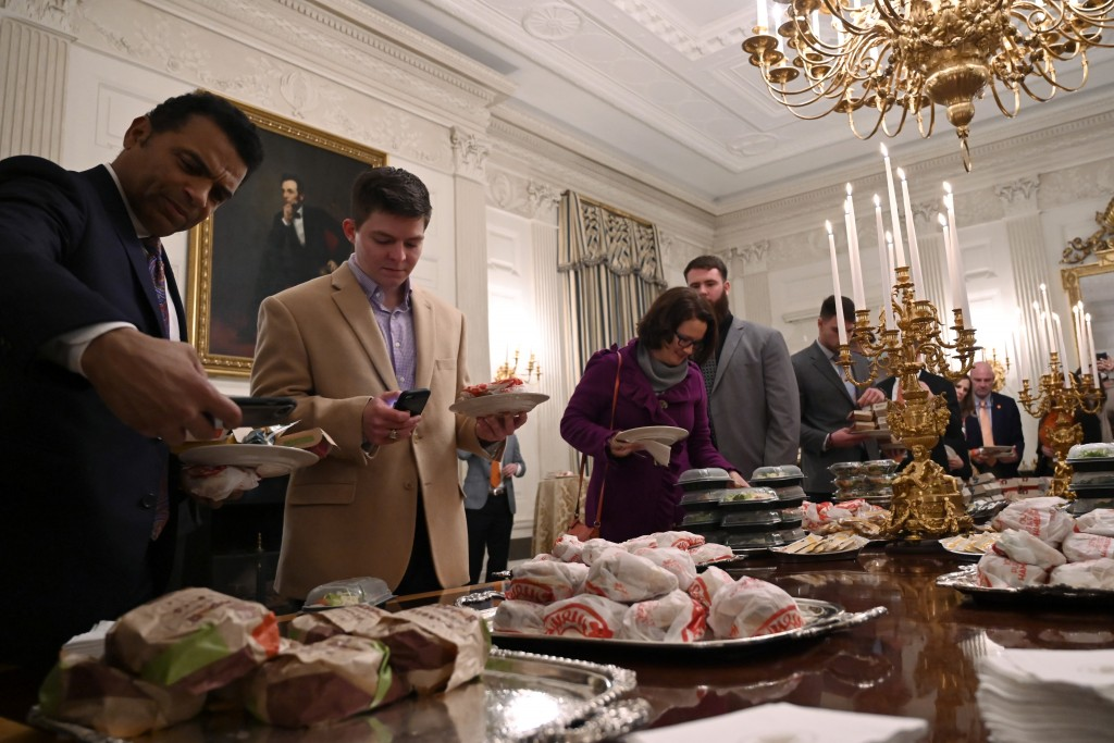FILE - In this Jan. 14, 2019, file photo, guests attending a reception for the Clemson NCAA college football team grab fast food sandwiches in the Sta...