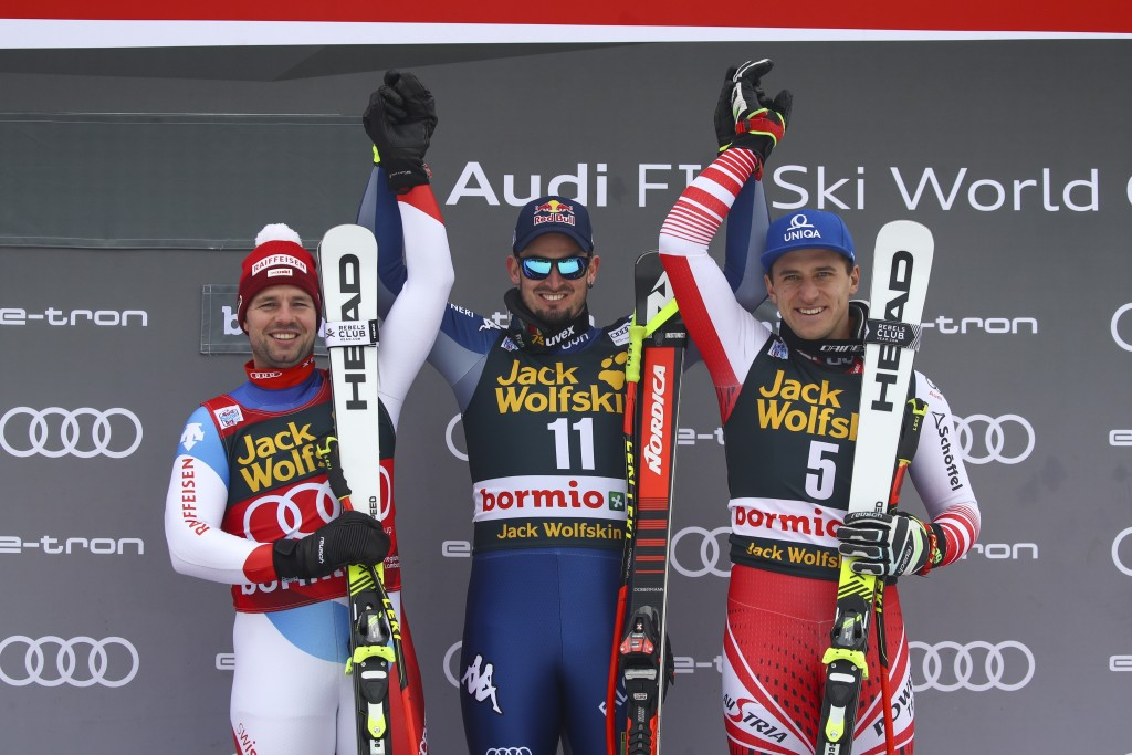 Italy's Dominik Paris, center, winner of an alpine ski, men's World Cup downhill, celebrates on the podium with second-placed Switzerland's Beat Feuz,...