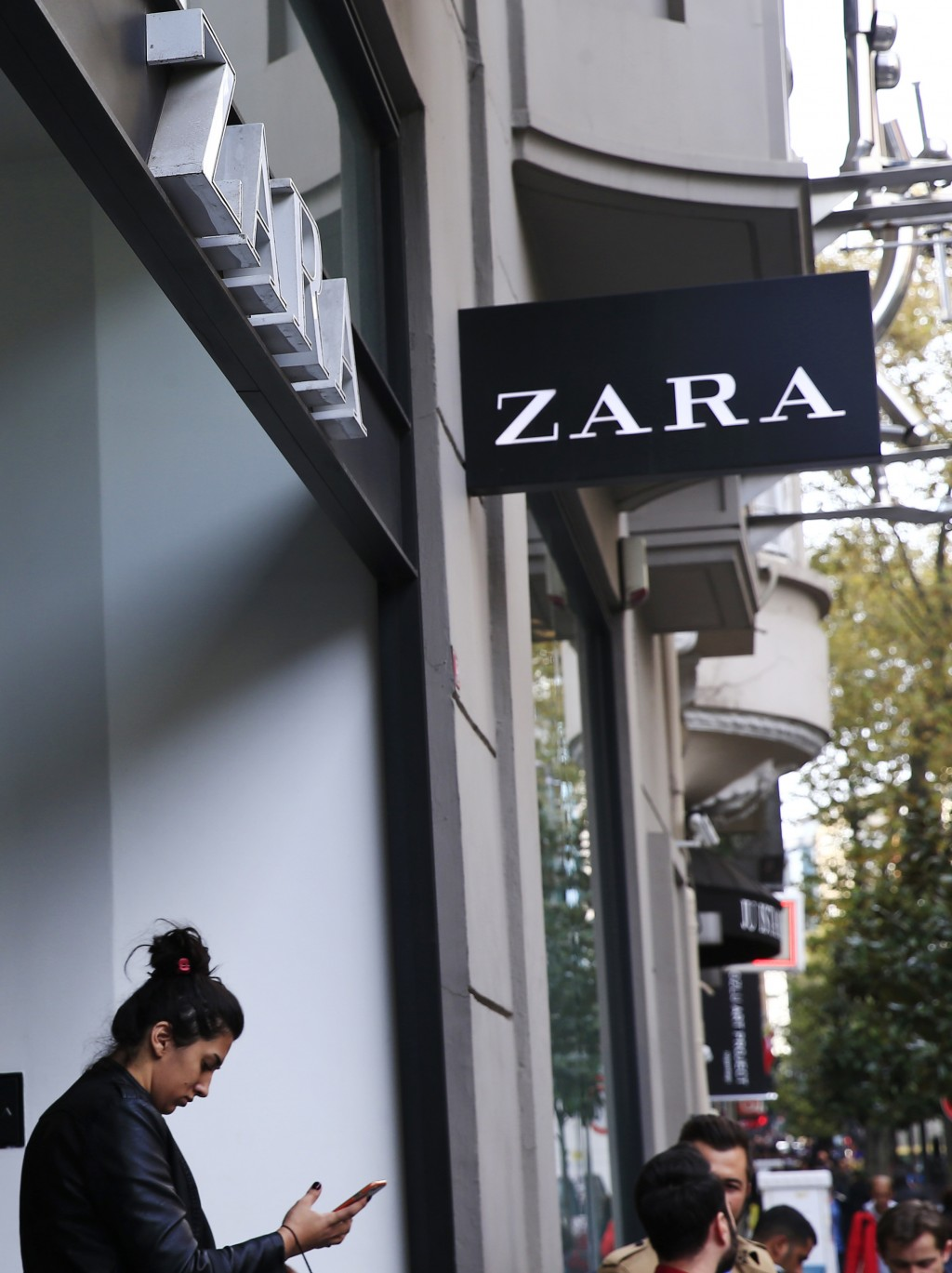 FILE - In this Friday, Nov. 3, 2017 file photo, a shopper exits a branch of fashion retailer Zara in an upscale Istanbul neighborhood. Inditex, the re...