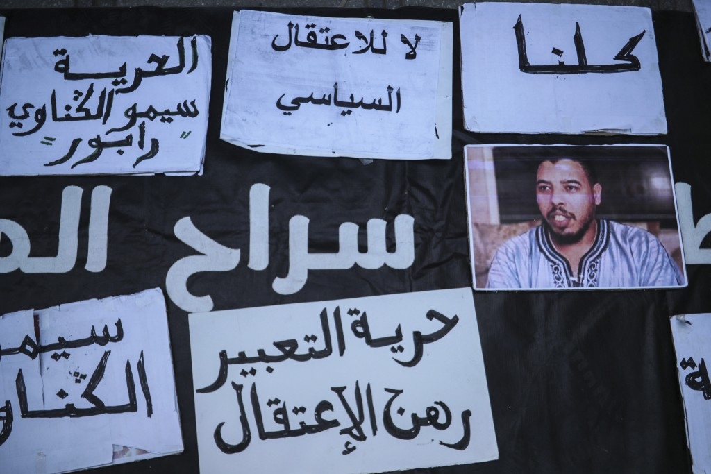 FILE - In this Monday, Nov. 25, 2019, photo, a photo of Moroccan rapper Gnawi is placed outside a court where he was on trial on charges of insulting ...