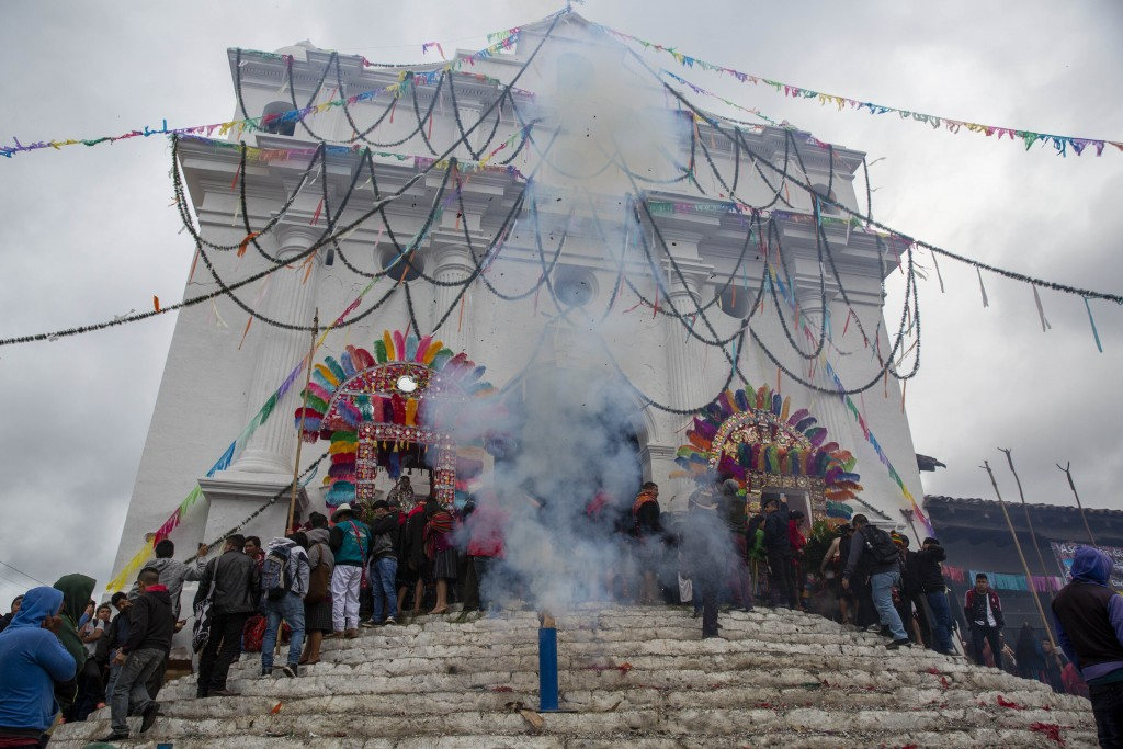 Locals launch fireworks from the steps of Saint Thomas church during celebration honoring the patron saint of Chichicastenango, Guatemala, Saturday, D...