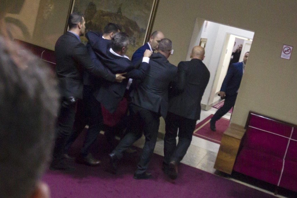 Police officers carry a pro-Serb opposition lawmaker in the parliament building in Podgorica, Montenegro, Friday, Dec. 27, 2019. The Serbian Orthodox ...