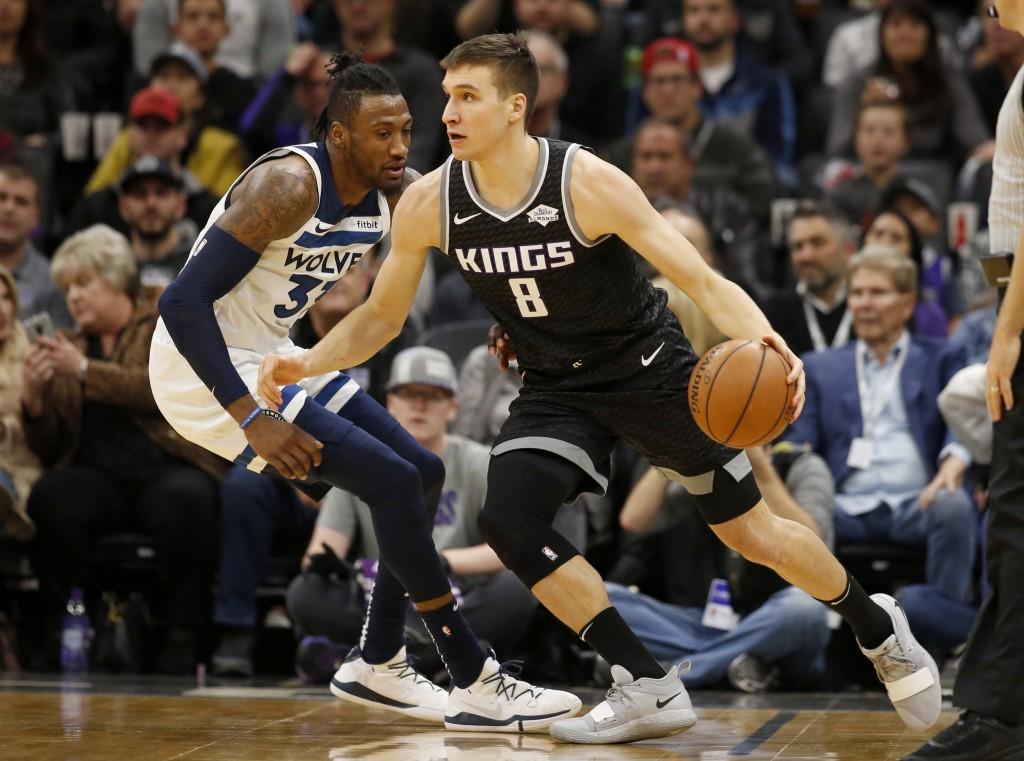 Sacramento Kings guard Bogdan Bogdanovic, right, drives against Minnesota Timberwolves forward Robert Covington during the first quarter of an NBA bas...