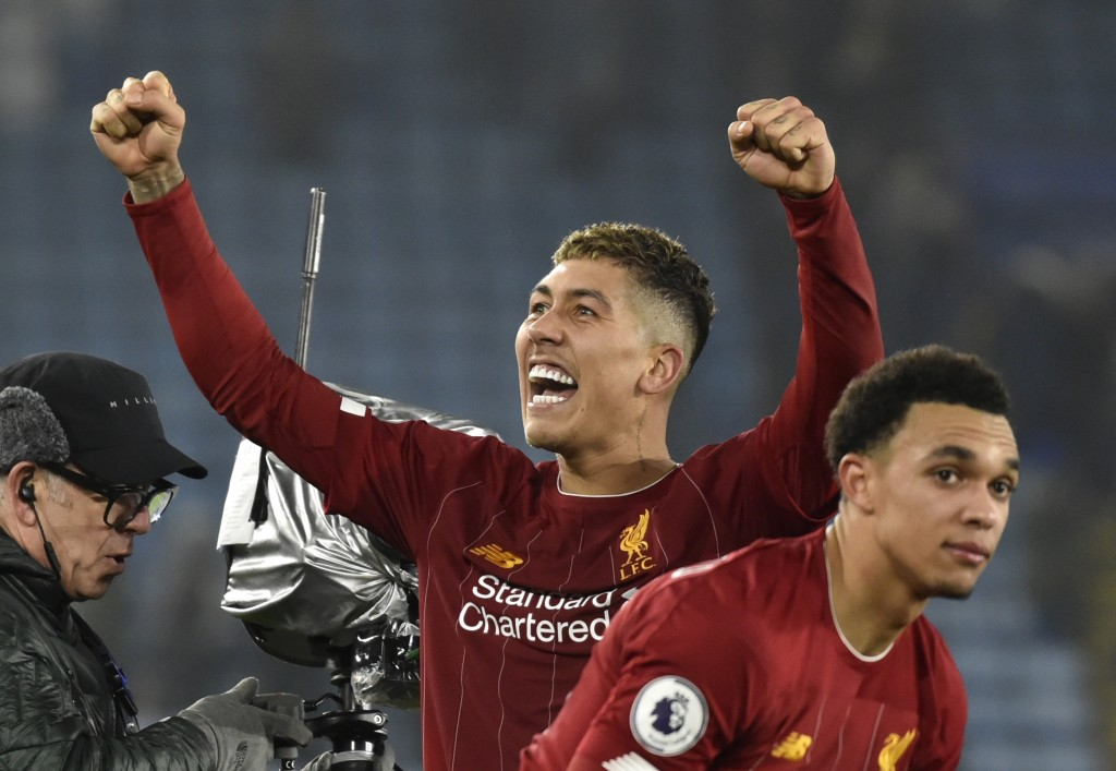 Liverpool's Roberto Firmino and Liverpool's Trent Alexander-Arnold celebrate their victory at the end of the English Premier League soccer match betwe...