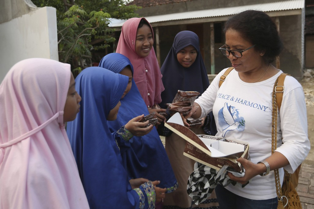 Ni Luh Erniati, right, gives cakes to Ali Fauzi's daughter and relatives while visiting Fauzi's home in Tenggulun, East Java, Indonesia, on Saturday, ...