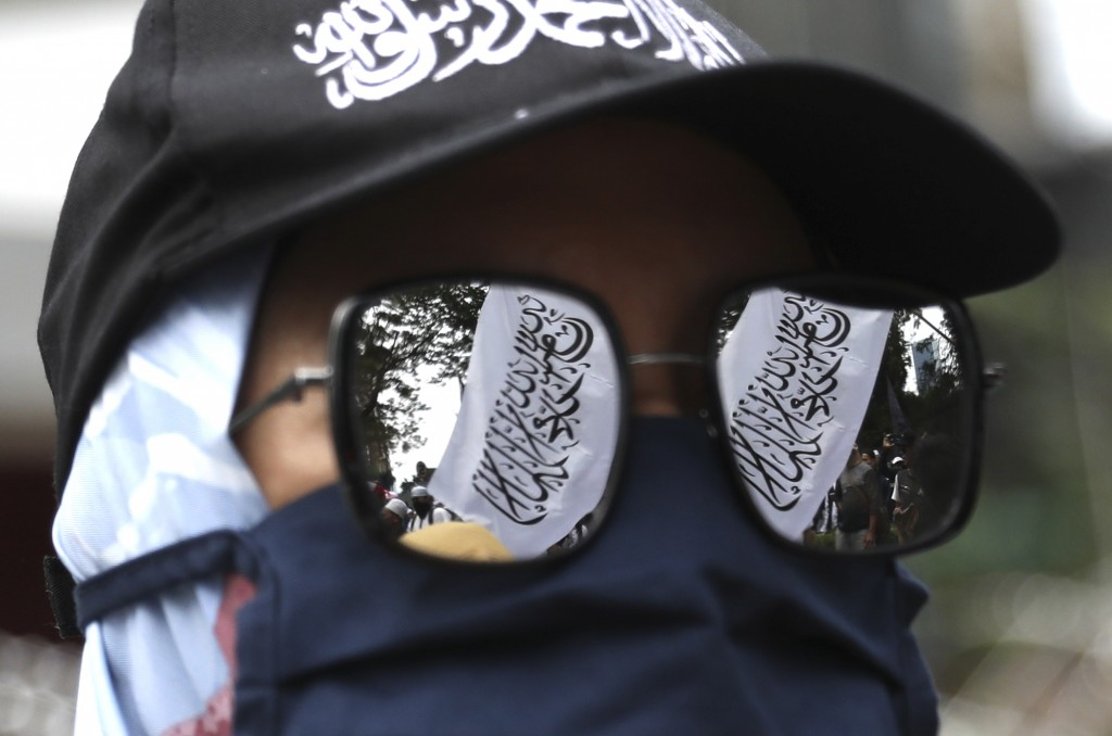 """A flag with Arabic writings that reads """"There's no God but Allah and Muhammad is his messenger"""" is reflected on the sun glasses of a Muslim woman duri..."""