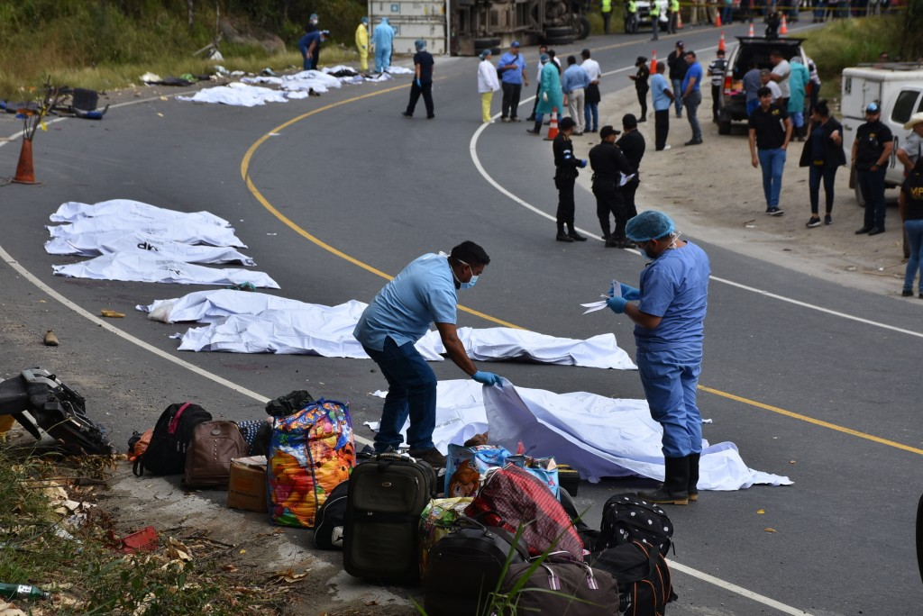 Forensic workers cover the bodies of passengers that perished in bus that crashed with a trailer truck in Gualan, Guatemala, Saturday, Dec. 21, 2019. ...