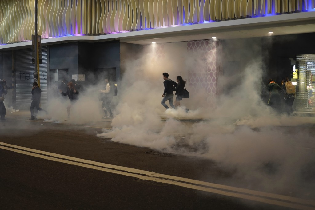 In this Tuesday, Dec. 24, 2019, file photo, residents react to teargas as police and protesters confront each other on Christmas Eve in Hong Kong. Mor...