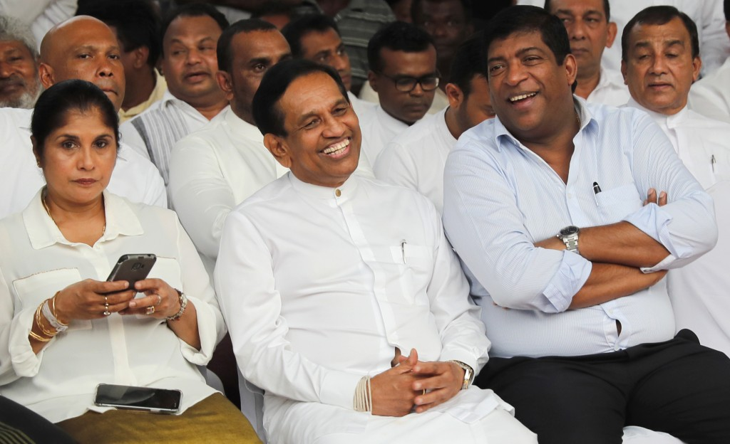 In this Monday, Dec. 23, 2019, photo, former Cabinet minister Rajitha Senaratne, center, sits with colleague Ravi Karunanayake during a protest in Col...