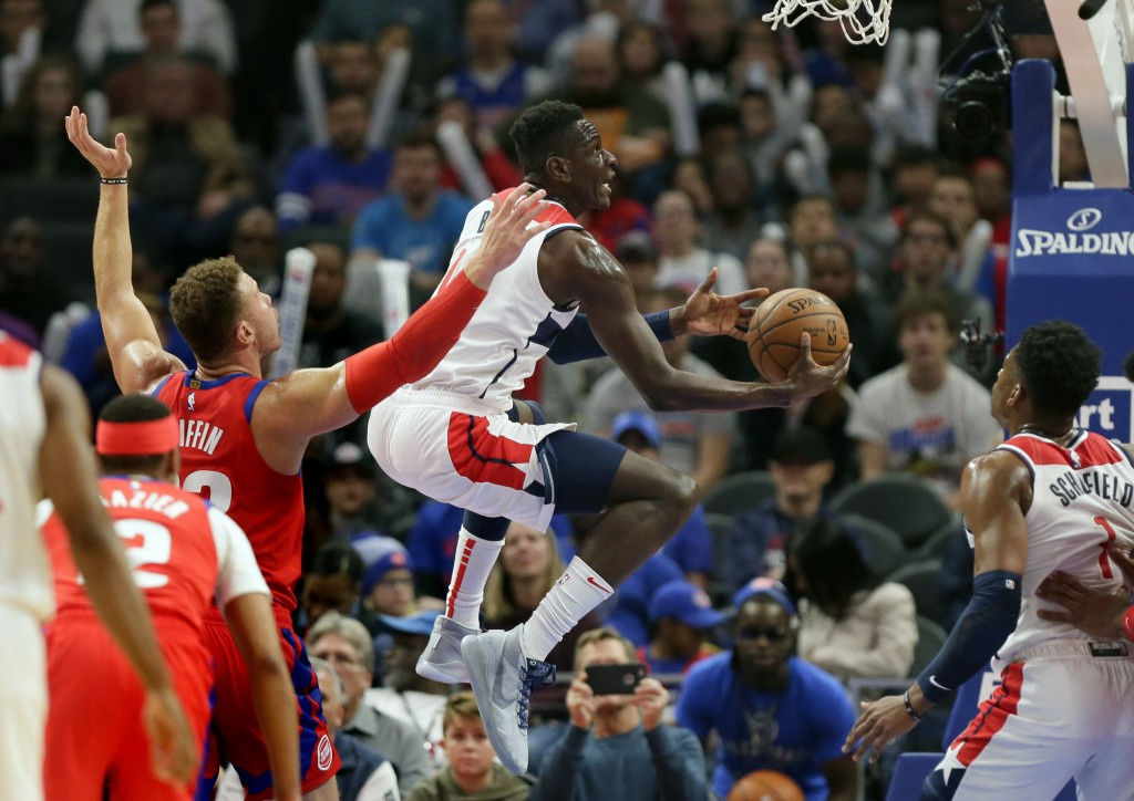 Washington Wizards guard Isaac Bonga, center, goes to the basket past Detroit Pistons forward Blake Griffin (23) during the first half of an NBA baske...