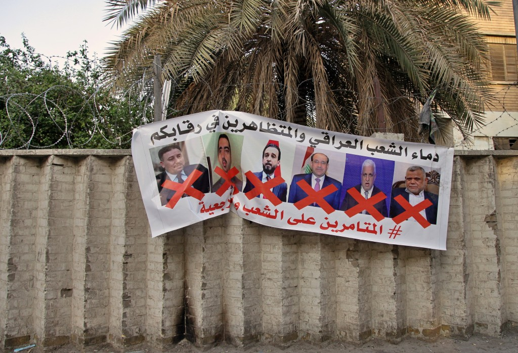 """A poster with defaced pictures of Iraqi politicians and Arabic that reads, """"the blood of the protesters and the Iraqi people is on your necks, the con..."""