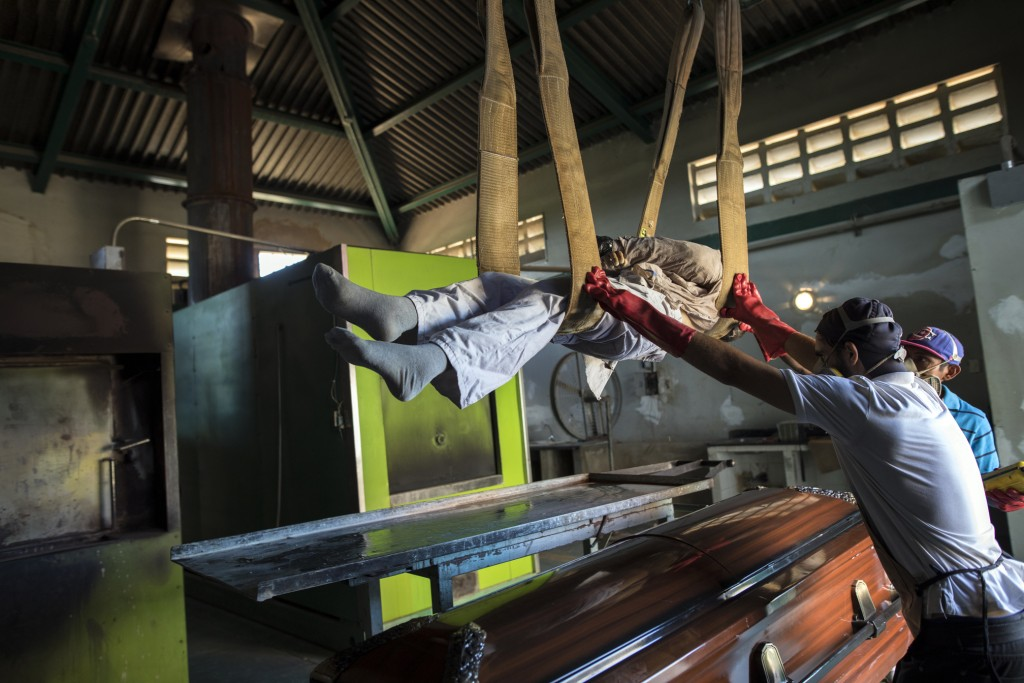 Cemetery workers lift a corpse from a coffin to a metal plate as they prepare the body for cremation at a cemetery in Maracaibo, Venezuela, Nov. 27, 2...