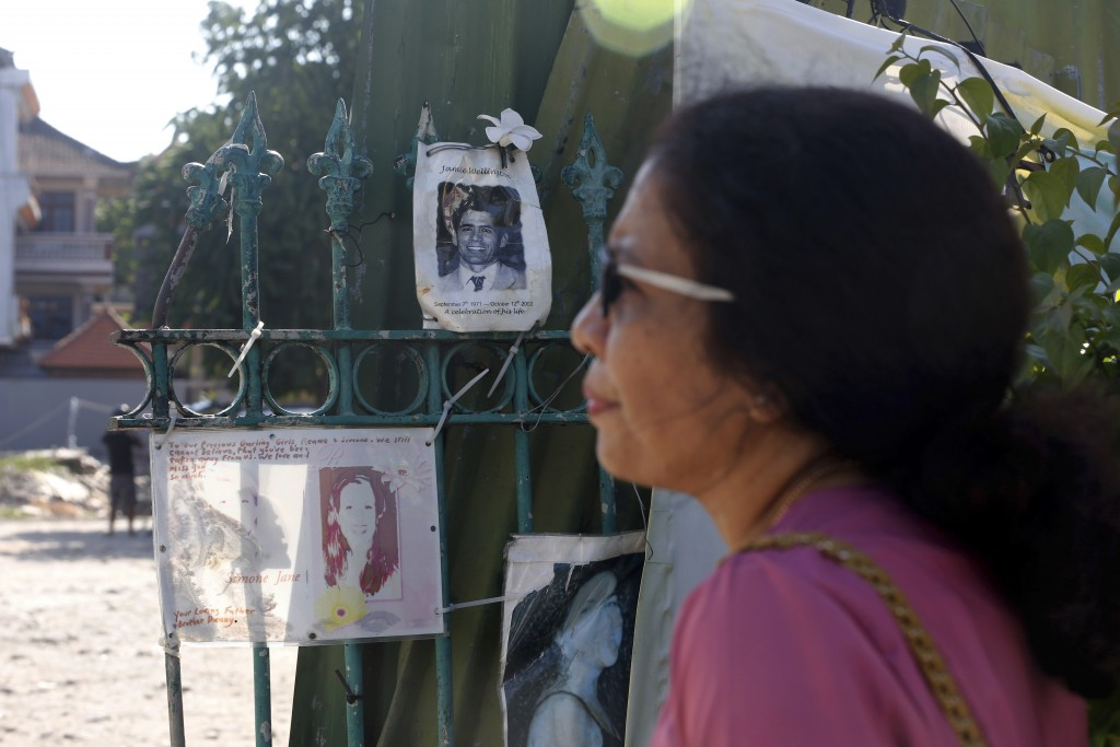 Ni Luh Erniati stands outside the site of the Sari Club bombing, with photographs of victims displayed on a gate in Bali, Indonesia on Friday, April 2...