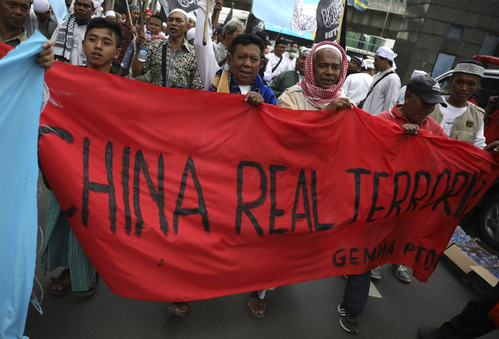 Muslim men hold a banner during a rally outside the Chinese Embassy in Jakarta, Indonesia, Friday, Dec. 27, 2019. Over a thousand Muslims staged the r...