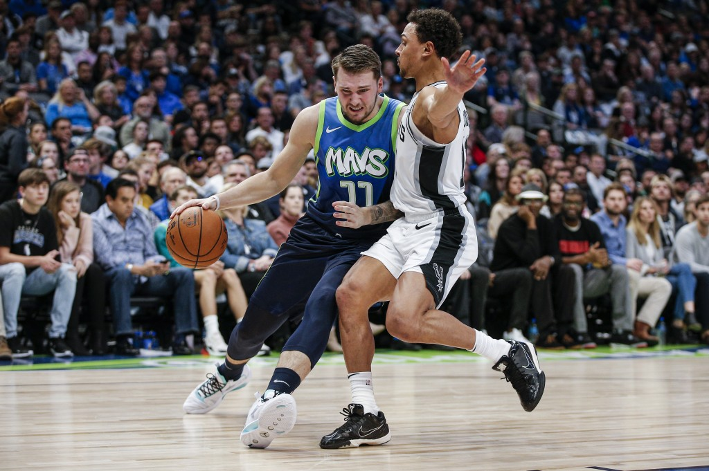 Dallas Mavericks forward Luka Doncic (77) battles San Antonio Spurs guard Bryn Forbes (11) for space during the first half of an NBA basketball game, ...