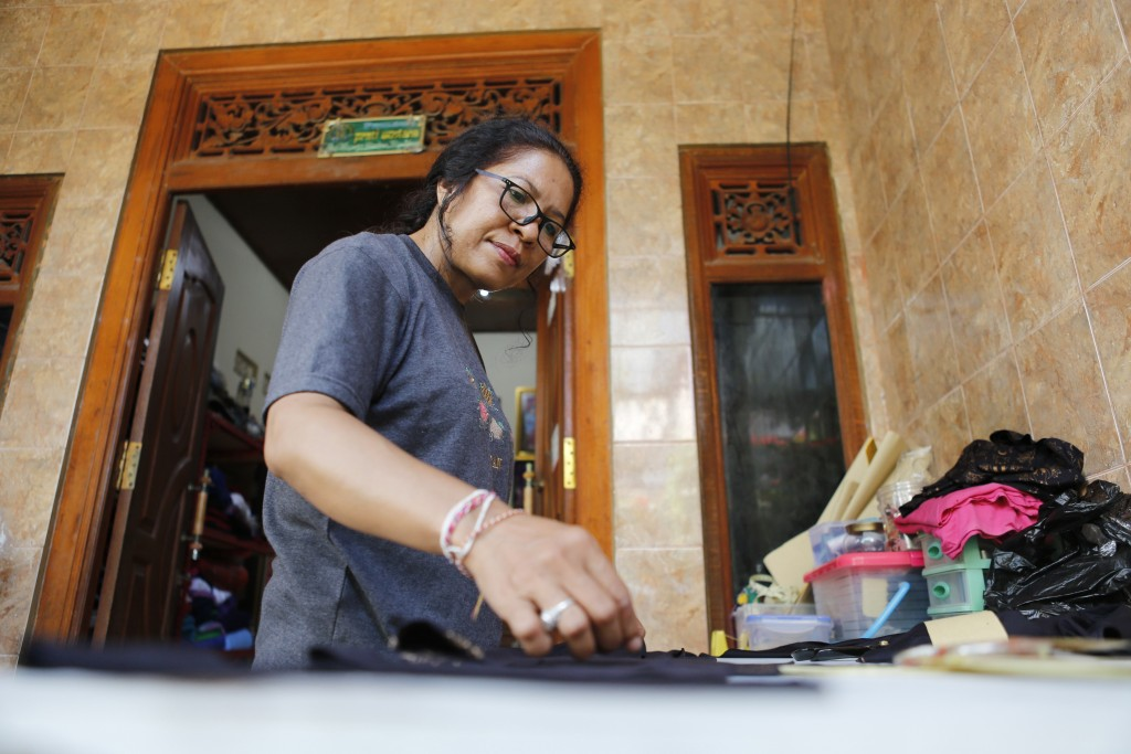 Ni Luh Erniati prepares to cut fabric to make a dress at her home in Bali, Indonesia on Thursday, April 25, 2019. After her husband was killed in the ...