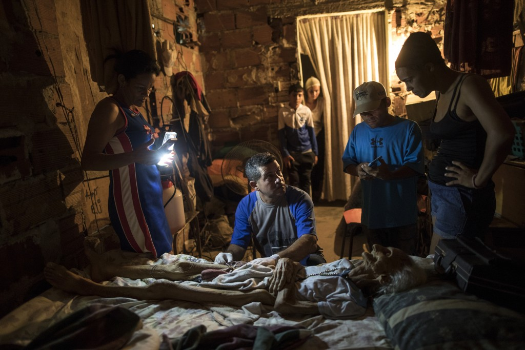 Community activist Carolina Leal uses a cell phone to light up the work area for Roberto Molero as he prepares the body of Teresa Jimenez, 91, after s...