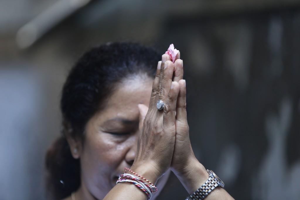 Ni Luh Erniati prays at a temple in her home in Bali, Indonesia on Friday, April 26, 2019. Erniati's husband, Gede Badrawan, was killed in the 2002 Ba...